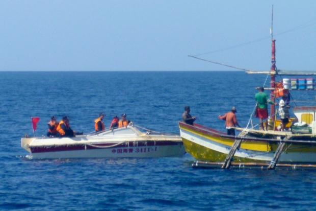 In this Feb. 27, 2015 file photo, Chinese Coast Guard members approach Filipino fishermen near Scarborough Shoal in the South China Sea. (AP / Renato Etac)