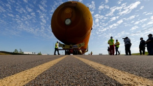 In this Sunday, April 10, 2016 photo, external Tank, ET- 94, NASA's only remaining space shuttle external tank, is transported by trailer to a dock at the NASA Michoud Assembly Facility in New Orleans. (AP Photo/Gerald Herbert)