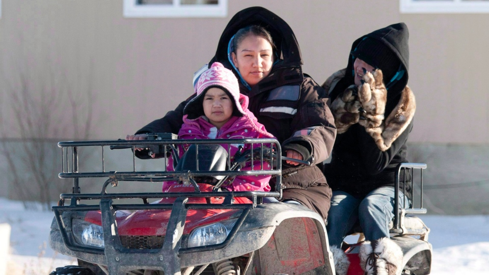 A woman takes children to school on a four-wheel vehicle following their lunch break in Attawapiskat, Ont., Tuesday November 29, 2011.(THE CANADIAN PRESS/Adrian Wyld)