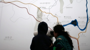 Visitors watch the North side on a foggy day through the glass showing a map of the Kaesong industrial park and the border area between North and South Koreas at the Imjingak Pavilion near the border village of the Panmunjom in Paju, South Korea, Saturday, April 9, 2016. (AP Photo / Lee Jin-man)