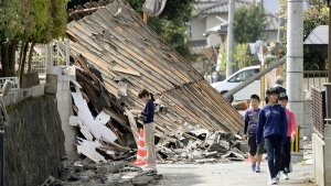 Children walk past a house collapsed by a magnitude-6.5 earthquake in Mashiki, Kumamoto Prefecture, southern Japan, Friday, April 15, 2016. (Koji Harada / Kyodo News via AP)