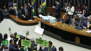"Brazil's Attorney General Jose Eduardo Cardozo, top left, presents the defense of Brazil's President Dilma Rousseff in the Chamber of Deputies, as opposition lawmakers hold signs that read in Portuguese ""Goodbye dear"" and ""Impeachment now"" in Brasilia, Brazil, Friday, April 15, 2016. (AP / Eraldo Peres)"