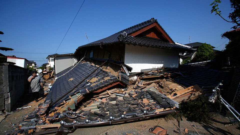A resident walks by a collapsed house in Mashiki, Kumamoto prefecture, southern Japan, Friday, April 15, 2016. (AP / Koji Ueda)