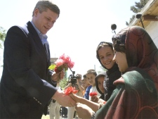 Canadian Prime Minister Stephen Harper receives flowers from students at the Aschiana school upon his arrival for a visit, in Kabul Afghanistan on May 22, 2007. (CP / Tom Hanson)