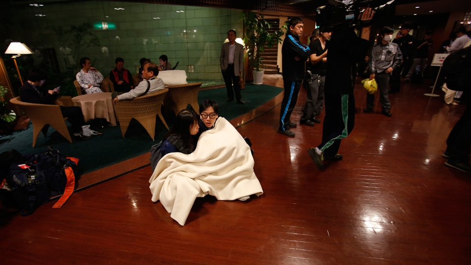 Hotel guests sit on the floor at the lobby in Mashiki, Kumamoto prefecture, southern Japan, early Saturday, April 16, 2016 after they evacuated their rooms and gathered at the hotel lobby. (AP / Koji Ueda)