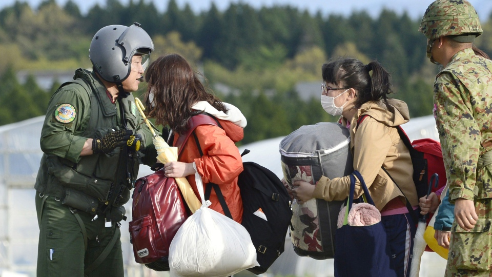 College students with their belongings wait for the arrival of a helicopter of the Japan Self-Defense Forces to be transferred to safer place in Minamiaso village, Kumamoto prefecture, Japan, Saturday, April 16, 2016. (Hiroko Harima/Kyodo News via AP)