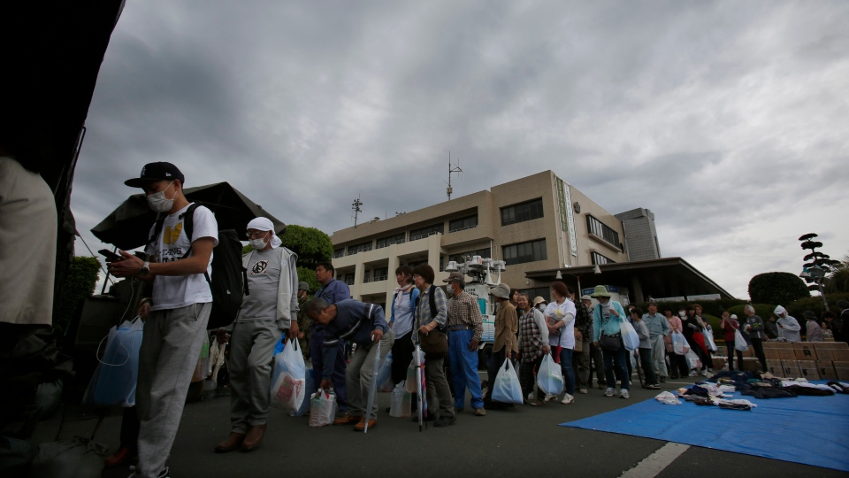 Local residents wait in line for rations of cooked rice at a distribution center in Mashiki, Kumamoto prefecture, southwestern Japan, Saturday, April 16, 2016. (AP / Koji Ueda)