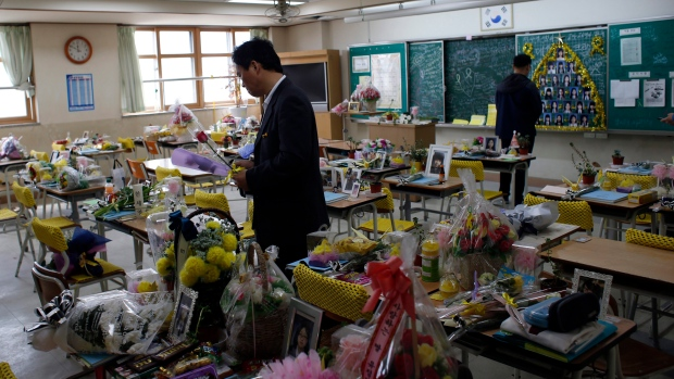 People visit a classroom as flowers, notes and snacks from classmates and families paying tribute to the victims of the sinking of ferry Sewol are placed on the desks, at the Danwon High School in Ansan, South Korea, Saturday, April 16, 2016. (AP / Lee Jin-man)