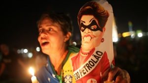 "An Anti-government demonstrator holds a caricature of Brazil's President Dilma Rousseff wearing a bandit mask and sash that reads in Portuguese ""Big oil"" outside Congress where lawmakers debate whether to oust the Brazil's President Dilma Rousseff in Brasilia, Brazil, Saturday, April 16, 2016. (AP / Eraldo Peres)"