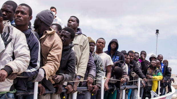 In this Sunday, May 31, 2015 file photo, migrants wait to disembark from the Italian Coast Guard ship Peluso, onto the tiny Italian island of Lampedusa. (AP / Mauro Buccarello, File)