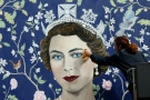 Workmen install a new mural by Frederick Wimsett, of Queen Elizabeth II to mark her 90th birthday celebrations, in central London, Tuesday, April, 19, 2016. (AP / Alastair Grant)
