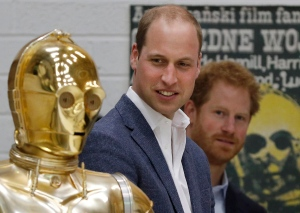 Prince William, centre and Prince Harry look at Star Wars character the droid C3P0 as they visit the creature and droid department at Pinewood studios in Iver Heath, west of London on Tuesday April 19, 2016. (Adrain Dennis, Pool Via AP)