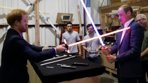 In this file photo, Prince William, right, and Prince Harry use lightsabers during a tour of the Star Wars sets at Pinewood studios in Iver Heath, west London, Tuesday April 19, 2016. (AP / Adrian Dennis)