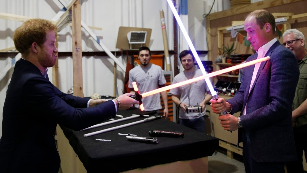 Prince William, right, and Prince Harry use light sabers during a tour of the Star Wars sets at Pinewood studios in Iver Heath, west London, Tuesday April 19, 2016. Prince William and Prince Harry toured Pinewood to visit the production workshops and meet the creative teams working behind the scenes on the Star Wars films. (Adrian Dennis/Pool via AP)