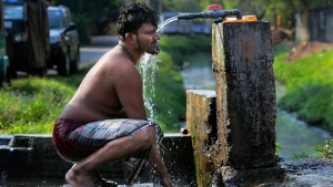 Taking a bath from a roadside tap in Colombo, Sri Lanka, on March 14, 2016. (Eranga Jayawardena / AP)