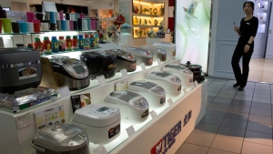 A sales girl past by rice cookers mostly imported from Japan on display at a shopping mall in Beijing, China, on April 20, 2016. (Ng Han Guan / AP)