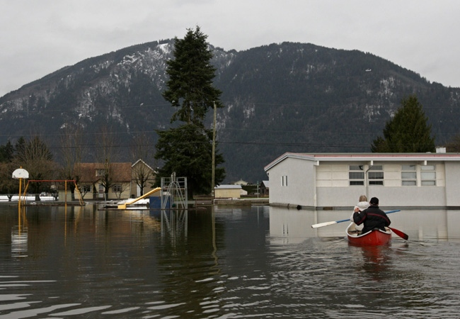 Eva Dueck, left, and her husband Roy paddle their canoe through a flooded school yard after checking on a neighbour in Chilliwack, B.C., on Friday, January 9, 2009. (THE CANADIAN PRESS/Darryl Dyck)