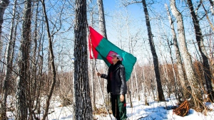 An indigenous junior ranger places a flag up at a youth bush camp where they teach survival skills in the northern Ontario First Nations reserve in Attawapiskat, Ont., on Tuesday, April 19, 2016. (THE CANADIAN PRESS/Nathan Denette)