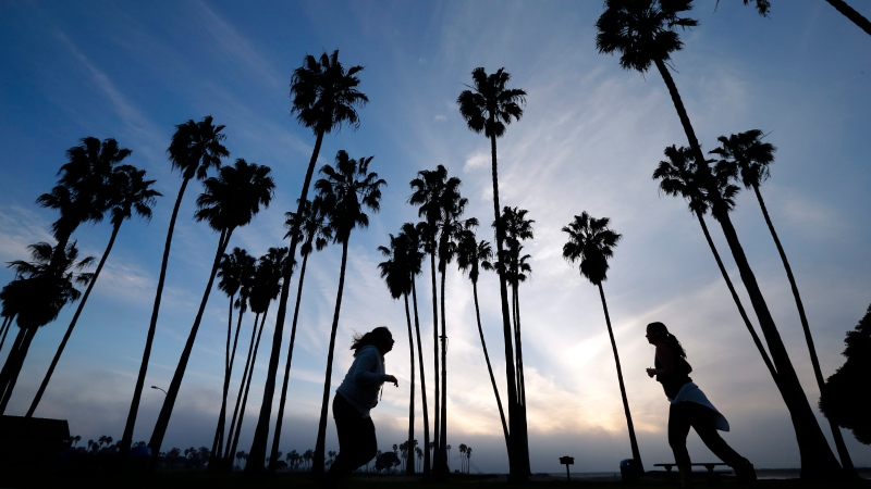 In this Feb. 23, 2016, file photo, women run as the sun sets in San Diego. (AP Photo/Gregory Bull, File)