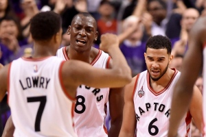 Toronto Raptors' Bismack Biyombo (8) celebrates with teammates Kyle Lowry (7) and Cory Joseph (6) after dunking on the Indiana Pacers during second half of game two, round one NBA basketball playoff action at the Air Canada Centre, in Toronto on April 18, 2016. (Frank Gunn / The Canadian Press)