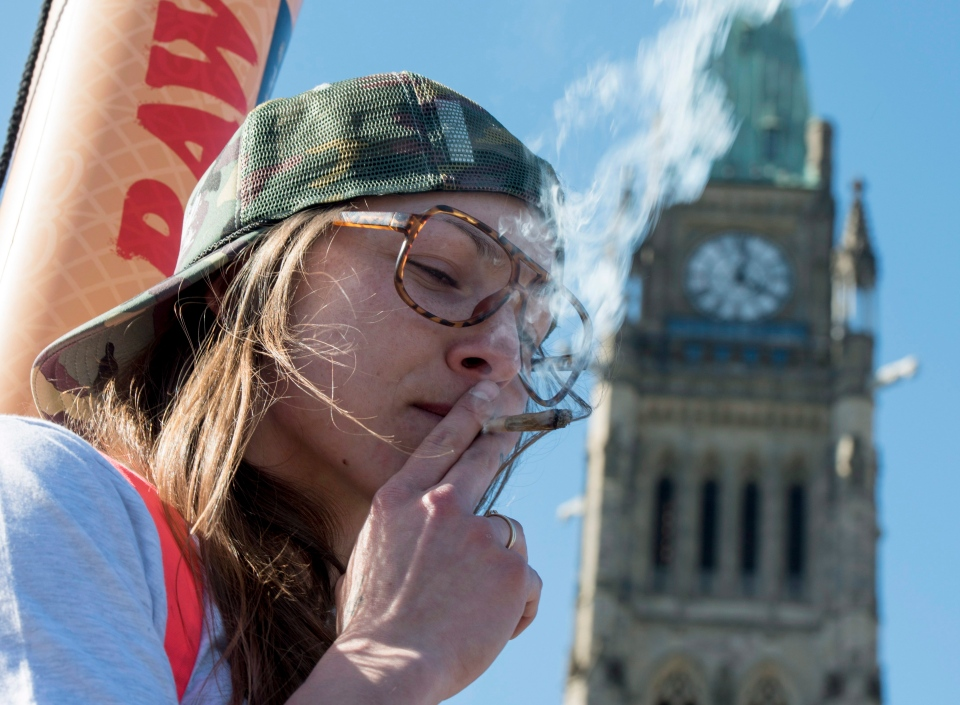A woman smokes a joint during the annual 420 marijuana rally on Parliament Hill on Wednesday, April 20, 2016 in Ottawa. (Justin Tang / THE CANADIAN PRESS)