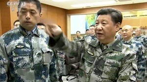 Chinese President Xi Jinping, right, in military uniform at the Joint Operation Command Center in Beijing.  (CCTV via AP Video)