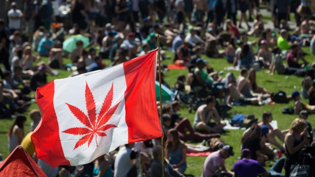 A marijuana flag flaps in the wind above the crowd at the annual 4-20 cannabis culture celebration at Sunset Beach in Vancouver, B.C., on Wednesday April 20, 2016. (Darryl Dyck / THE CANADIAN PRESS)