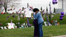 Fans embrace by a makeshift memorial for Prince