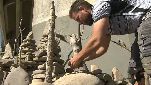 It takes him several days to stack the rocks and he has to contend with some vandalism.