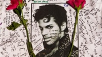 Flowers lay on a T-shirt signed by fans of singer Prince at a makeshift memorial place created outside Apollo Theatre in New York, Friday, April 22, 2016. The pop star died Thursday at the age of 57. (AP / Andres Kudacki)