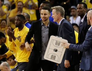 Golden State Warriors' Stephen Curry, centre, and coach Steve Kerr smile during a timeout during the first half in Game 2 of a first-round NBA basketball playoff series against the Houston Rockets on April 18, 2016, in Oakland, Calif. (Ben Margot / AP Photo)