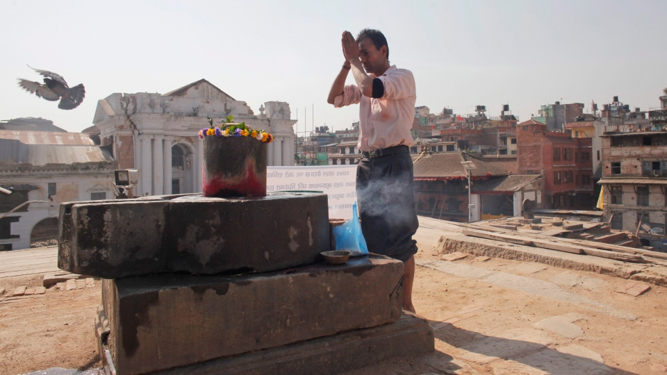 A Nepalese man offers prayers in front of a 'Siva Lingam', symbolic of Hindu god Shiva, as he worships at a temple that was completely destroyed in last year's earthquake at the Basantapur Durbar Square in Kathmandu, Nepal, Sunday, April 24, 2016. (AP / Niranjan Shrestha)