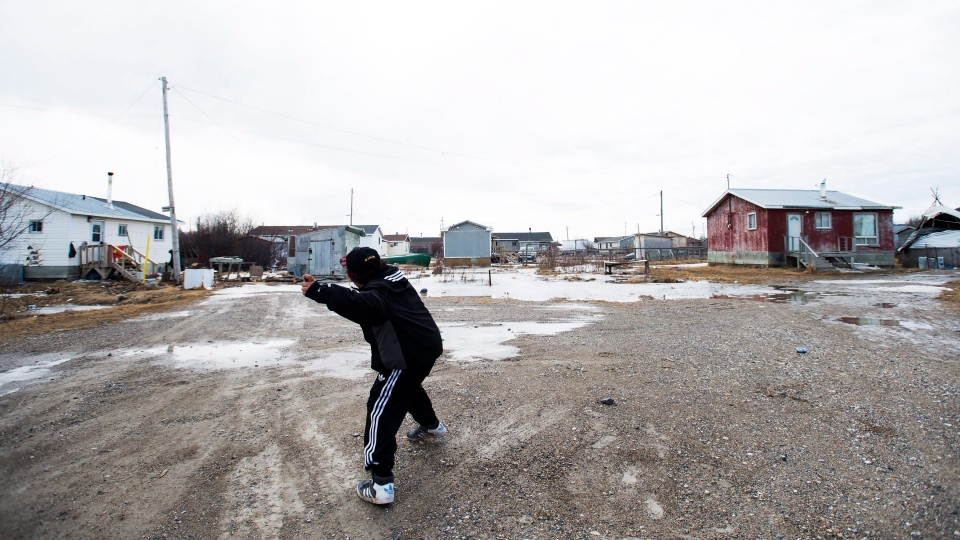 Teenage boys throw rocks in the northern Ontario First Nations reserve in Attawapiskat, Ont., on Monday, April 16, 2016. (Nathan Denette / THE CANADIAN PRESS)