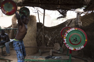 A man lifts a barbell at the MM Club, a weight room in the neighbourhood of Dapoya, Ouagadougou. (AFP PHOTO / NABILA EL HADAD)