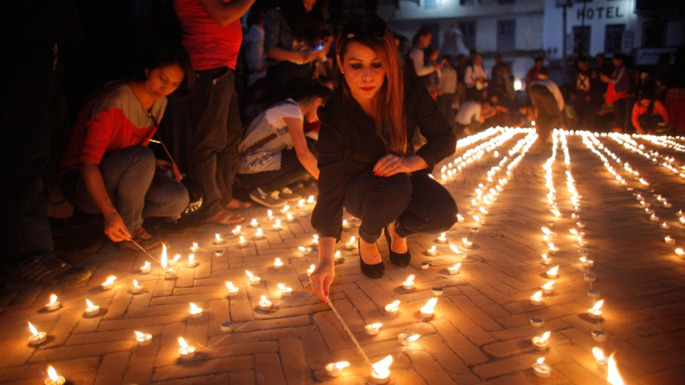 Nepalese people light candles in memory of those who died in last year's devastating earthquake in Basantapur Durbar Square in Kathmandu, Nepal, Sunday, April 24, 2016. Nepalese held memorial services to mark the anniversary of the disaster that killed nearly 9,000 people and left millions homeless. (Niranjan Shrestha / AP)