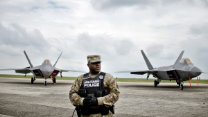 A U.S. military policeman stands in front of U.S. Air Force F-22 Raptor fighter jets that were flown to the Mihail Kogalniceanu air base, near the Black Sea port of Constanta in southeast Romania, Monday, April 25, 2016. (AP / Andreea Alexandru)