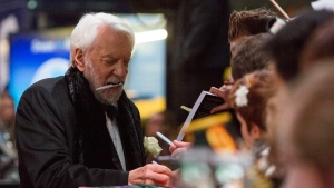 "Canadian actor Donald Sutherland signs autographs before the world premiere of the movie ""The Hunger Games: Mockingjay - Part 2"" in Berlin, Germany, Wednesday, Nov. 4, 2015. (AP / Gero Breloer)"