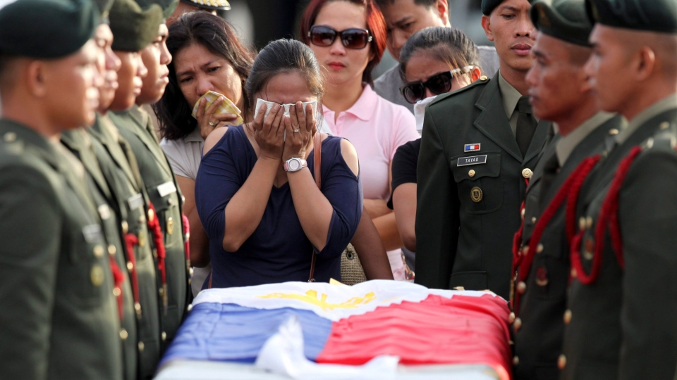 Relatives grieve at the flag-draped casket of one of the soldiers killed in clashes with Abu Sayyaf militants in the Philippines, on Saturday, June 21, 2014. (AP Photo/Bullit Marquez)