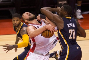 Toronto Raptors' Jonas Valanciunas and Indiana Pacers' Ian Mahinmi, 28, battle for the ball during second half, round one NBA basketball playoff action in Toronto on April 18, 2016. (Mark Blinch / The Canadian Press)