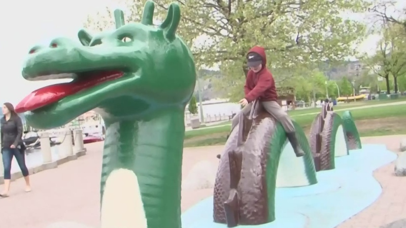 A child plays on a statue of Ogopogo in this file photo from 2016.