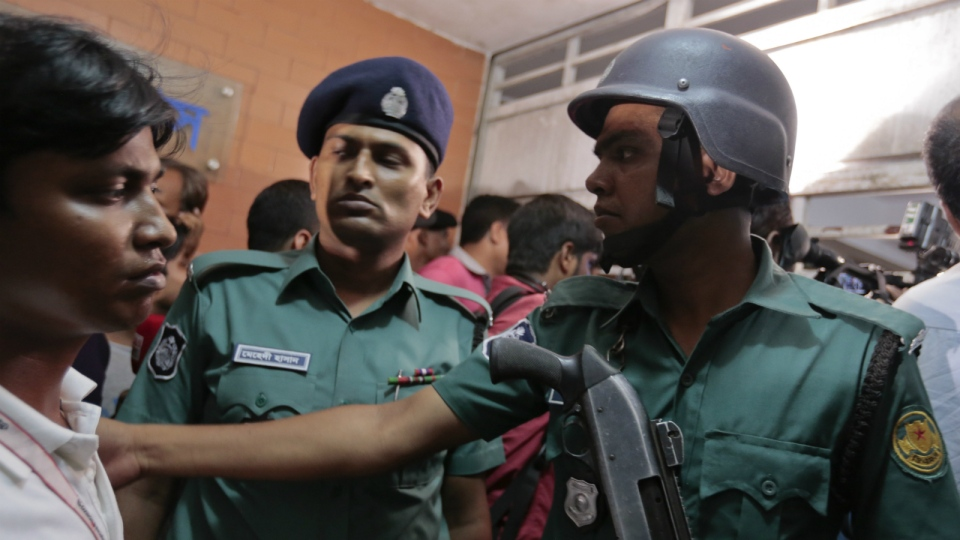 Bangladeshi policemen try to control the crowd of onlookers at a building where two people were found stabbed to death in Dhaka, Bangladesh on Monday, April 25, 2016. (AP / A.M.Ahad)