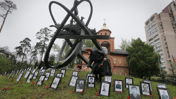 A relative of a Chernobyl victim lays flowers at the photos near the monument erected in memory of the victims of the Chernobyl explosion in Ukraine's capital Kyiv, Ukraine, Tuesday, April 26, 2016. (AP / Efrem Lukatsky)