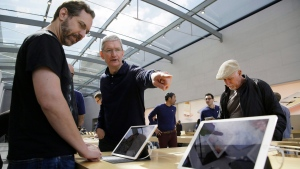 Apple CEO Tim Cook points out the new 9.7 inch iPad Pro to a customer during a visit to the Apple store, in Palo Alto, Calif., on Thursday, March 31, 2016. (AP Photo/Eric Risberg)