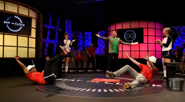 "In this Tuesday, March 31, 2015 photo, host Elliott Morgan, back, stands over contestants Greg Edwards, left, and Mark Schroeder as they finish a contest during a taping of the classic game show ""Beat the Clock,"" at YouTube Space LA in Los Angeles. (Photo by Chris Pizzello / Invision / AP)"