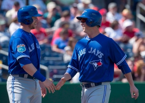 Toronto Blue Jays third baseman Matt Dominguez (right) is congratulated by Justin Smoak after scoring on the Philadelphia Phillies on a double by Darwin Barney in the third inning of Spring Training action in Clearwater, Fla. on March 1, 2016. (Frank Gunn / The Canadian Press)