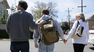 Sam Alexander and Ellen Schneider help their son, Ben, cross a street on their way to lunch in New Orleans. When Ben was about 2 1/2 he was diagnosed with autism. (AP / Jonathan Bachman)