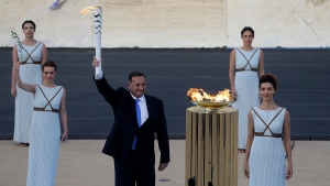 The head of Greece's Olympic Committee, Spyros Capralos, left, holds the torch with the Olympic Flame as actress Katerina Lehou as high priestess stands next to the cauldron during the handover ceremony at Panathinean stadium in Athens, Wednesday, April 27, 2016. (AP / Thanassis Stavrakis)