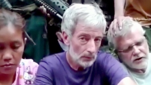 FILE - This image made from an undated militant video that surfaced in 2015, shows Canadians John Ridsdel, right, and Robert Hall, centre. (Militant Video via AP Video)