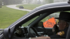 Leonard Manley, left, father and grandfather of several murder victims, drives up Union Hill Road away from a roadblock at the outer perimeter of a crime scene near Piketon, Ohio on Wednesday, April 27, 2016. (AP / John Minchillo)