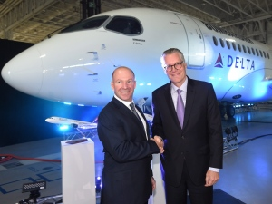 Alain Bellemare, left, president and CEO of Bombardier Inc., and Ed Bastian, right, CEO of Delta Air Lines, shake hands in front of a Delta-branded Bombardier C-Series jet in Mirabel, Que., on Thursday, April 28, 2016. (Ryan Remiorz / THE CANADIAN PRESS)